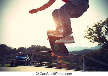 skateboarder legs doing a ollie at skatepark