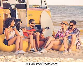 Summer fun. Group of joyful young people drinking beer and...