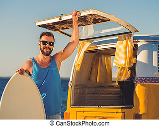 Finally summer! Smiling young man leaning at the skimboard and holding hand on door of car trunk while standing on the beach