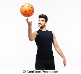 Basketball player spinning ball on his finger isolated on a...