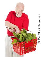 Senior Shopper Checks Basket - Senior man checking his...