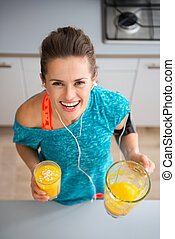 Athletic smiling woman holding freshly-made smoothie in...