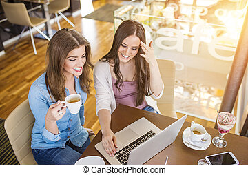 Two beautiful women with laptop in cafe