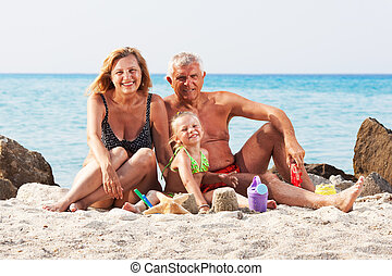 Little girl with grandparents on the beach - Happy Little...