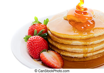 Pancakes and strawberry with maple syrup poured on top
