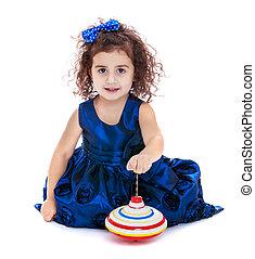 Little girl spinning dreidel sitting on the floor-isolated...