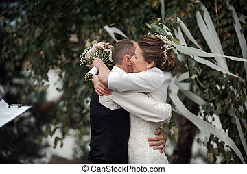 wedding ceremony - beautiful bride hugging groom at wedding...