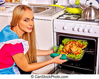 Woman cooking chicken at kitchen - Young blond beautiful...