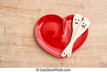 Wooden kitchen utensils on red hearth plate. Funny food...