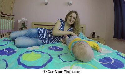 mom and baby play on bed - smiling young mother have fun...