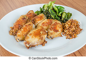 Fried chicken wings over white dish on wooden table