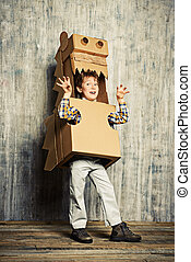 childhood - Little dreamer boy playing with a cardboard...