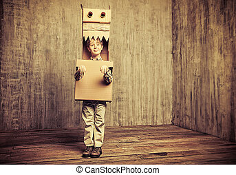 old toys - Funny dreamer boy playing with a cardboard...