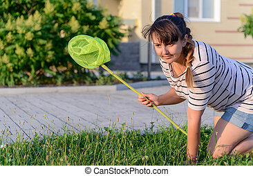 Young Woman Crawling on Lawn with Bug Net Searching for...