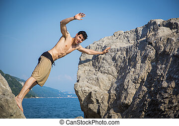 Young Man Spanning Gap Between Coastal Boulders - Handsome...