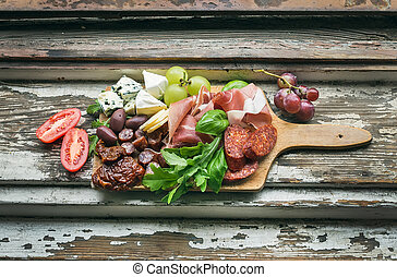 Meat appetizers selection on the old painted wood background...