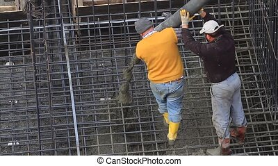 Two workers pulling the large hose of a concrete pumping...