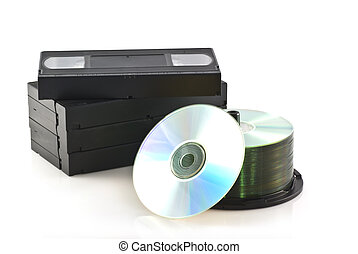 Videotapes versus dvd. - Videotapes and a pile of DVDs on a...