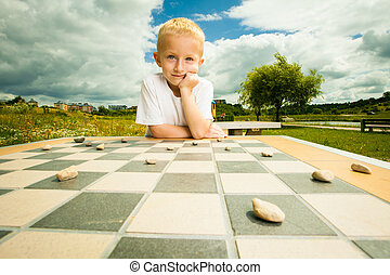 Child playing draughts or checkers board game outdoor -...