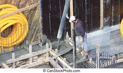 Construction man pouring cement on concrete footings for a...