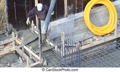 Construction worker during concrete pouring work at the...