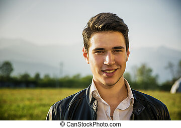 Handsome smiling young man at countryside, in front of field...