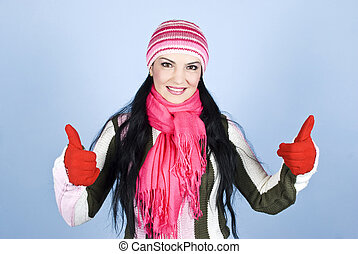 Successful happy winter woman giving thumbs up with gloves...
