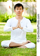 Man Meditating - An attractive asian man meditating outdoors...