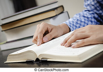 Reading text book - A young woman reading a book in the...