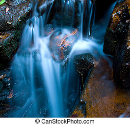 gushing waterfall - a gushing waterfall flowing over the...