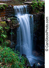 small waterfall - a small waterfall flowing over a small...