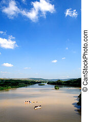 clear blue sky above a river with people caneoing on it