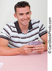playing card games - a smiling young man playing a game of...