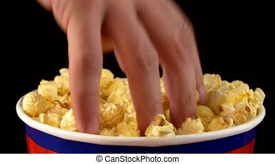 Hands grabbing popcorn on black, rotation - Hands grabbing...