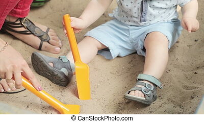 Mom with baby sandbox - Close up of baby boy on hands at...