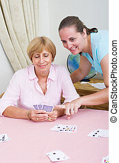learning card games - a young woman teaching a senior woman...
