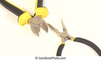 Needle-nose pliers and mini cutters on white, rotation,...