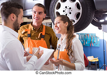 Client at auto service - Mechanics helping insurance agent...