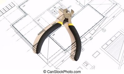 Wire cutters with yellow, gray handle on building plan,...