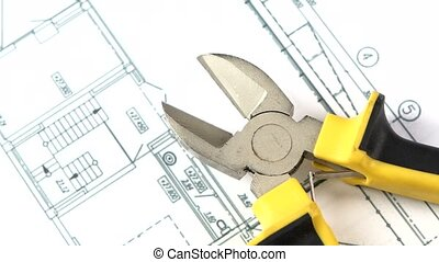 Cutting pliers on building plan, scheme, rotation, close up...