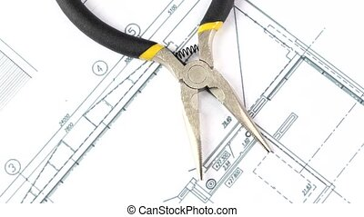 Gray and yellow round-nose pliers on building plan, scheme, rotation, close up