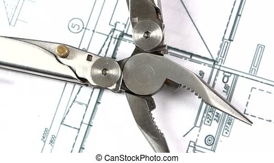 Metal round-nose pliers on building plan, scheme, rotation,...