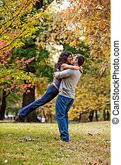 Propose - A man and woman hugging in a park
