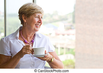 senior woman with tea - a senior woman holding a cup of tea...