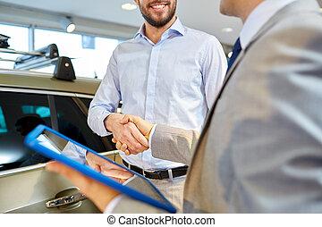 happy man shaking hands in auto show or salon - auto...