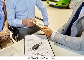 customers giving money to car dealer in auto salon - auto...