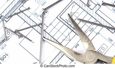 Gray and yellow round-nose pliers on building plan, scheme...