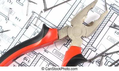 Gray and red pliers on building plan, scheme among nails,...