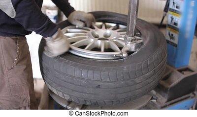 Mechanic repair wheel - Mechanic in the service repair car...