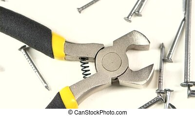 Wire cutters with yellow, gray handle on white among nails,...